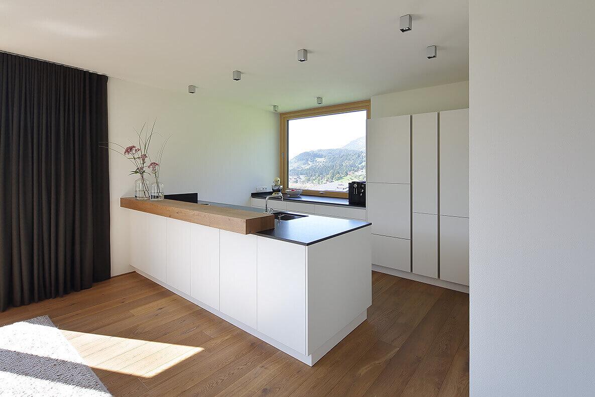 Weiße Küche mit schwarzer Arbeitsplatte und Bartheke aus Holz von Hartmann - die Tischler.